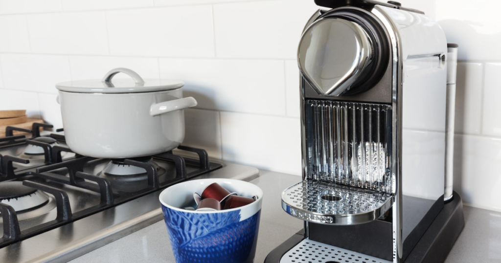 Image of one of the best pod coffee machines and some coffee pods in a small bowl