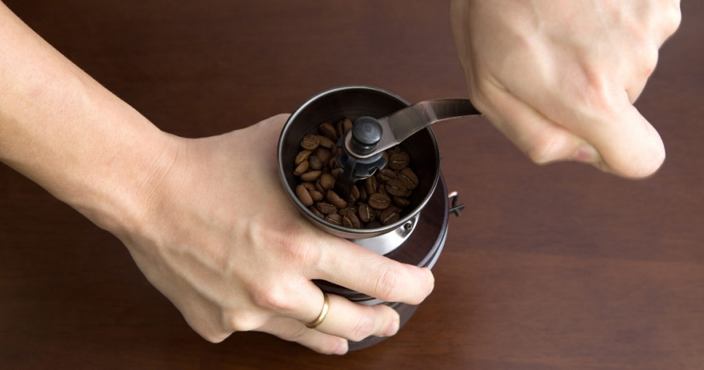 an image of the best manual coffee grinder starting to grind some coffee beans